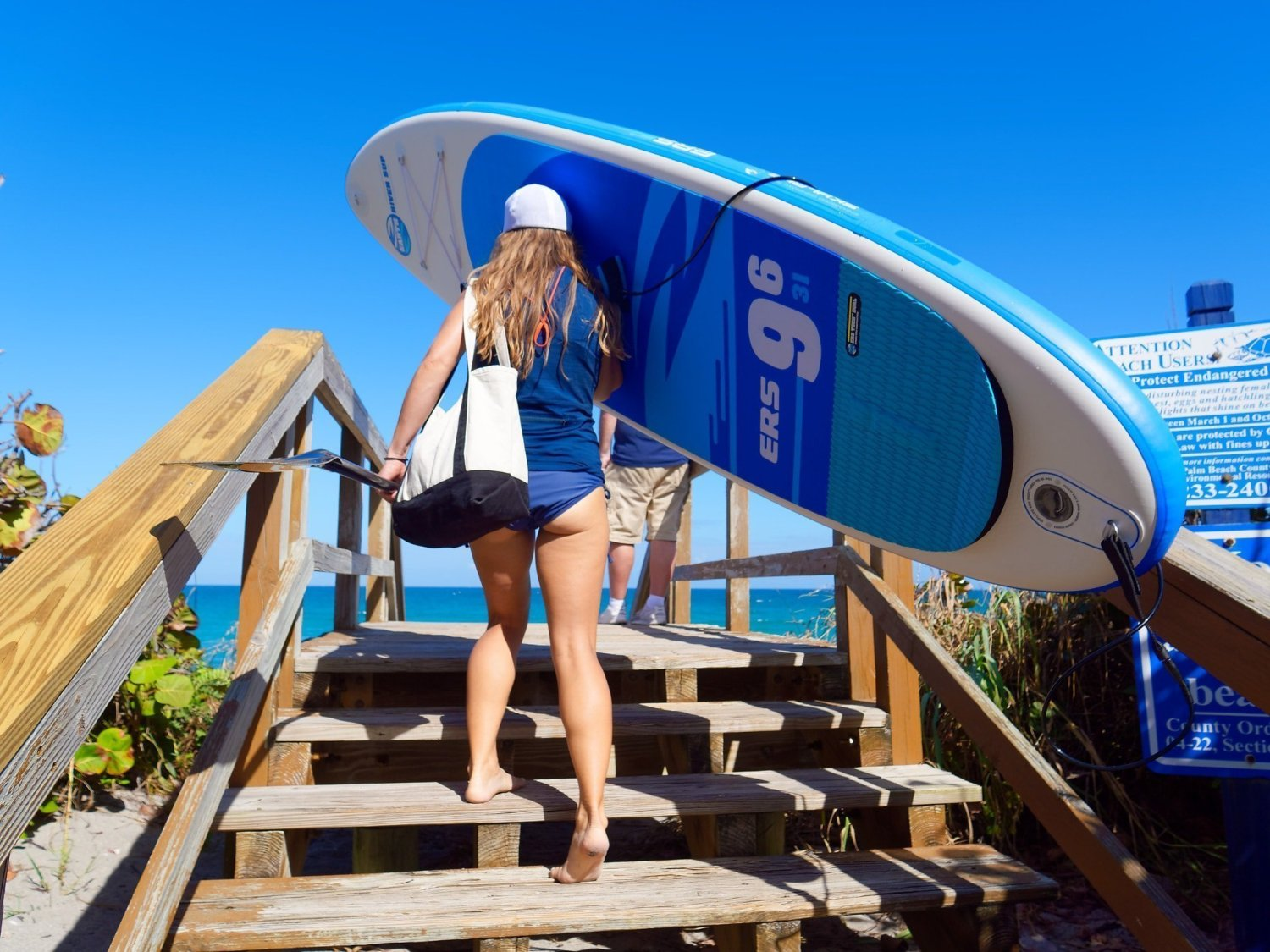 girl carrying a lightweight inflatable SUP up stairs