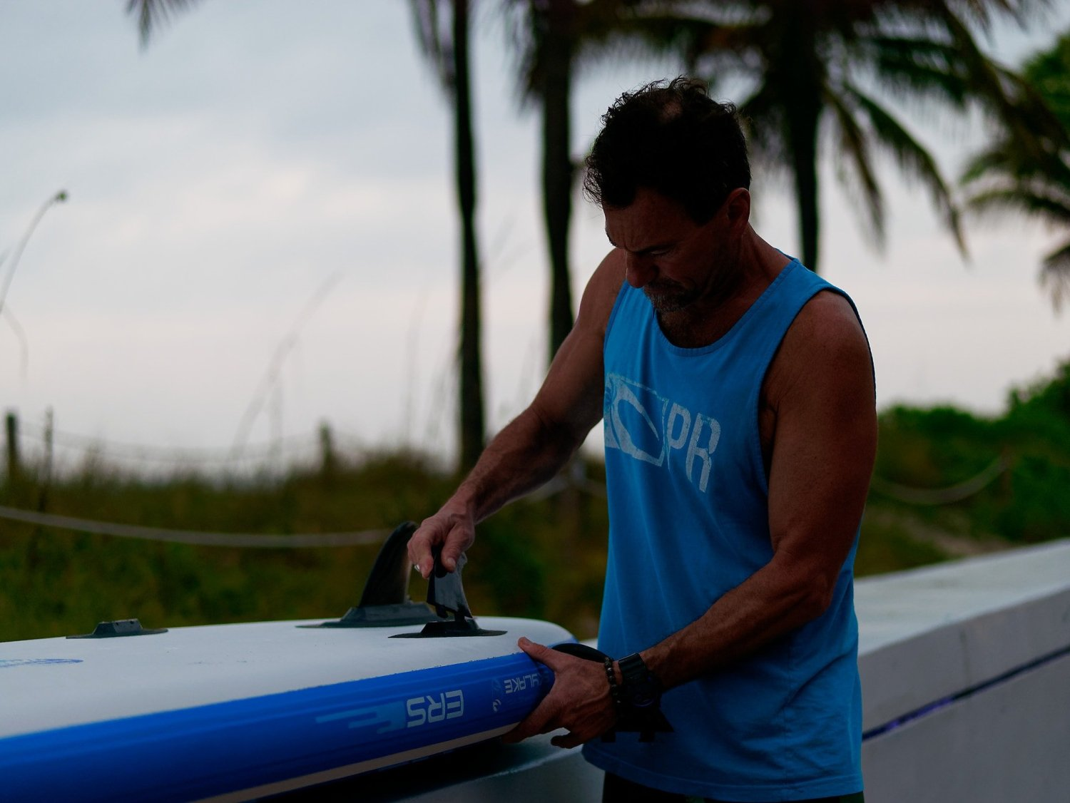 man fitting fins to a paddle board