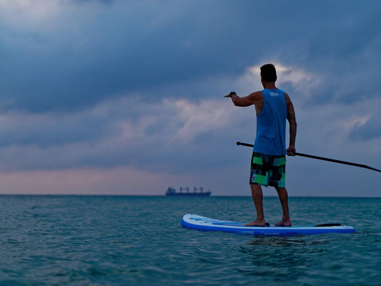 Greg Miller paddling on a flat ocean