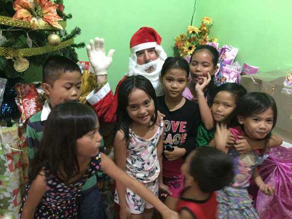 Several happy children stand in front of Santa at a party in the Philippines