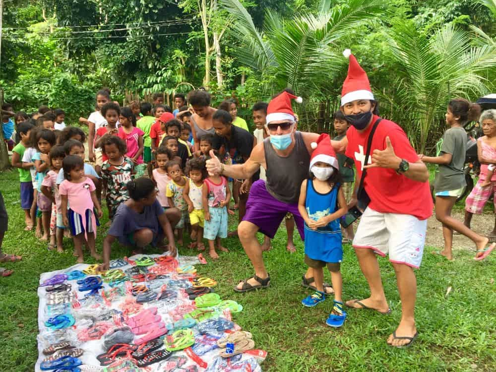 The start of the early Christmas for the Ati with children lined up for shoes, and Santa's helpers wearing hats.
