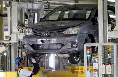 An Indonesian worker inspects a passenger car at the Toyota plant in Karawang, West Java, Indonesia. (Photo: AAP).