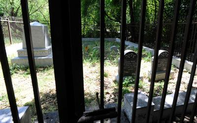 John Muir's burial site is photographed about a mile south of the Muir Homestead in a quiet, fenced in tree-shaded area near the banks of Alhambra Creek on Monday, April 29, 2013, in Martinez, Calif. John Muir, the champion of wilderness, died of pneumonia on Christmas Eve in 1914 in Southern California while visiting his younger daughter, Helen. Dr. John Strentzel, John Muir's father-in-law, is buried at left while John Muir, second from right is next to his wife, Louie (Louisa) Strentzel Muir. (Susan Tripp Pollard/Bay Area News Group)