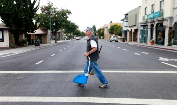 Michael Lydon crosses Piedmont Avenue at Pleasant Hill Road to continue cleaning both sides of the street in Oakland, Calif., on Friday, Aug. 22, 2014. Since 1979 Lydon has voluntarily helped keep Piedmont Avenue clean and welcoming. (Laura A. Oda/Bay Area News Group)