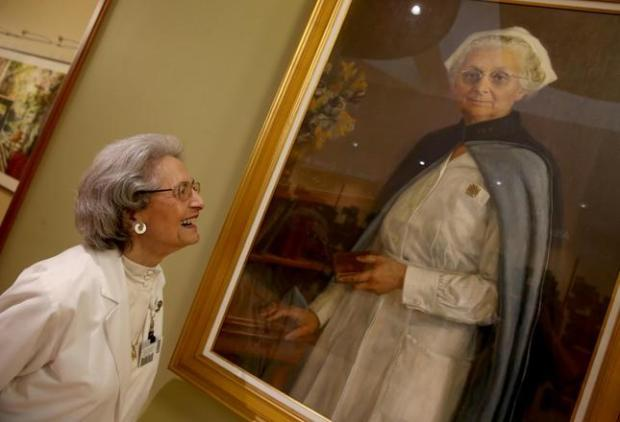 Elena Griffing looks at a photo of Alta Bates at Sutter Health Alta Bates Summit Medical Center in Berkeley, Calif., on Friday, April 8, 2016. Griffing, of Berkeley, who recently turned 90, celebrated her 70th year of working at the hospital on April 10. Griffin worked with Bates when she first began her job. (Jane Tyska/Bay Area News Group)