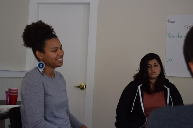 """Zuleika Lewis, a conference coordination for Community Works West in Oakland, with community member Rosy Corado-Biggs, talk to a young offender during a Sept. 29 """"restorative community conference"""" in Oakland."""