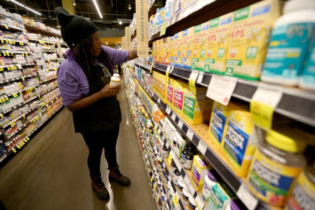Whole Foods employee Cherice Lewis organizes items at the store in Oakland, Calif., on Tuesday, Oct. 18, 2016. (Anda Chu/Bay Area News Group)
