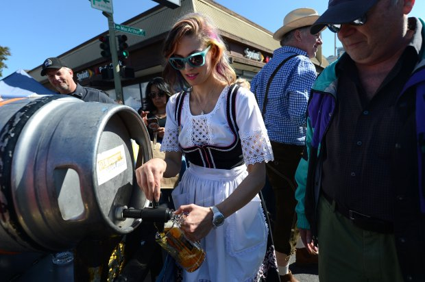 Christine Knobel, of Berkeley, pours beer at the ninth annual Oaktoberfest in the Dimond District on Oct. 1, 2016. (Dan Honda/Staff archives)