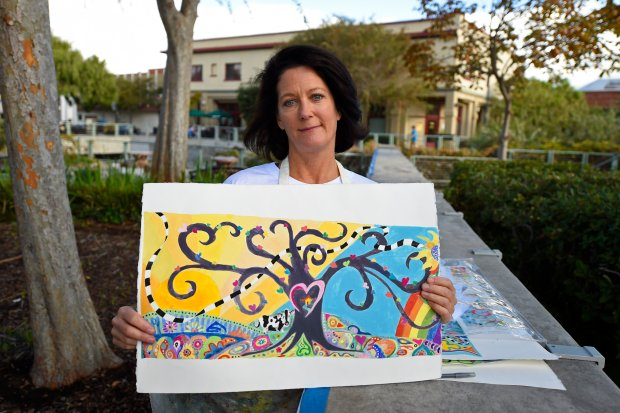Artist Colleen Gianatiempo, of Martinez, holds a drawing of the mural she is creating on a wall at the Main Street Plaza in Martinez, Calif. on Saturday, Oct. 29, 2016. The mural is called Small Town With a Big Heart. The mural is a way to thank the community for the support for the Betti family since the tragic passing of their 14 year-old daughter Jenna, who died in a train accident in March of 2014. The community is being asked to participate by helping paint the mural. More information can be obtained at www.hersmile.org (Jose Carlos Fajardo/Bay Area News Group)