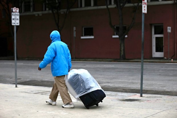 A pedestrian walks with a suitcase covered in plastic as people prepare for the first storm of the fall in San Jose, Calif., on Friday, October 14, 2016. (Josie Lepe/Bay Area News Group)