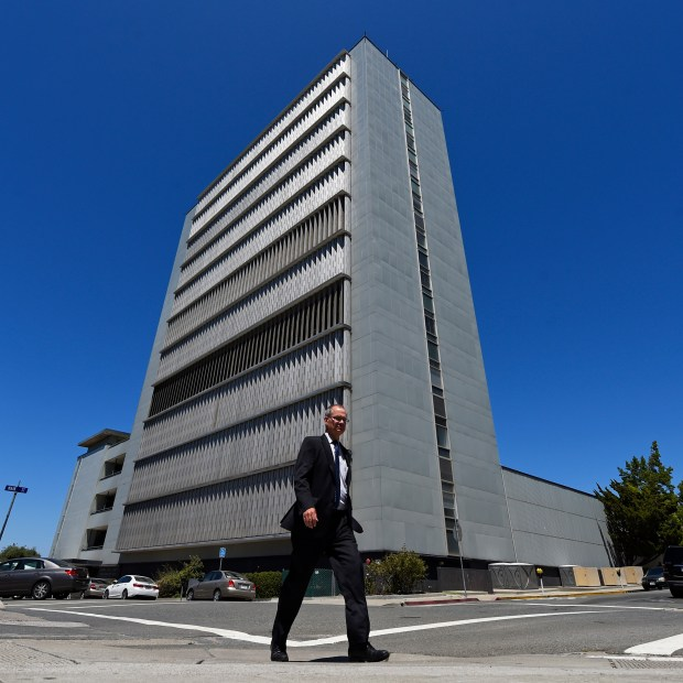 A pedestrian crosses the street in front of the Contra Costa County Administration Building in Martinez, Calif., on Thursday, Aug. 4, 2016. Contra Costa County hopes to replace the main county administration building in downtown Martinez. The late-1950's 12-story structure, where approximately 200 people work and where the county supervisors meet most Tuesdays, is the tallest building in Contra Costa County. (Jose Carlos Fajardo/Bay Area News Group)