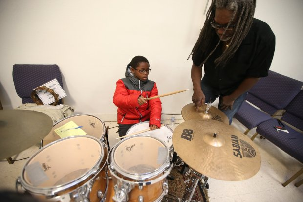 Sadiq Hasan ,7, is photographed at a drum set with Bobby Eddings, right, at the East Bay Church of Religious Science on Sunday, Nov. 20, 2016, in Oakland, Calif. Edding's works with the Family, Art, Community, Education, Spirituality organization to offer free weekly drum and bass guitar lessons for children and teens at the church. (Aric Crabb/Bay Area News Group)