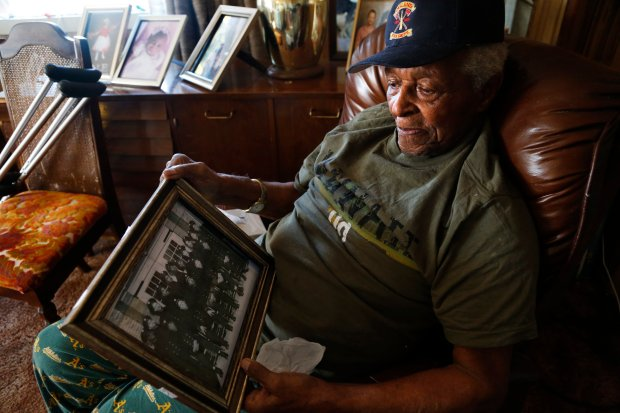 Milton Williams, 95, talks about being an Oakland firefighter back in 1948 while holding a photo of him and fellow black firefighters at his home in Oakland, Calif., on Wednesday, Nov. 16, 2016.  When he was hired, the fire department was still segregated. Williams has been a recipient of the Meals on Wheels program for about ten years, allowing him to live at his home of 40 years. (Laura A. Oda/Bay Area News Group)