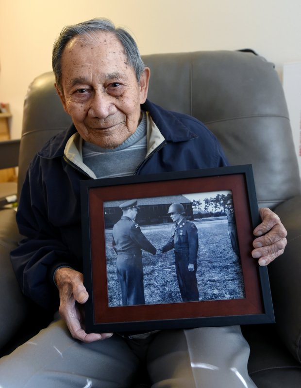 Janny Ruiz, 98, survived the Bataan Death March and fought with the 45th Infantry Regiment, a unit of the Philippine Scouts, as he holds a photo of himself from the 1950's when he was serving in Korea as he shares his story at his home in Hercules, Calif., on Thursday, Dec. 29, 2016. Even though it came very late, many Filipino soldiers were denied the full military benefits they had been promised, the awarding of the gold medal is nonetheless appreciated. (Susan Tripp Pollard/Bay Area News Group)