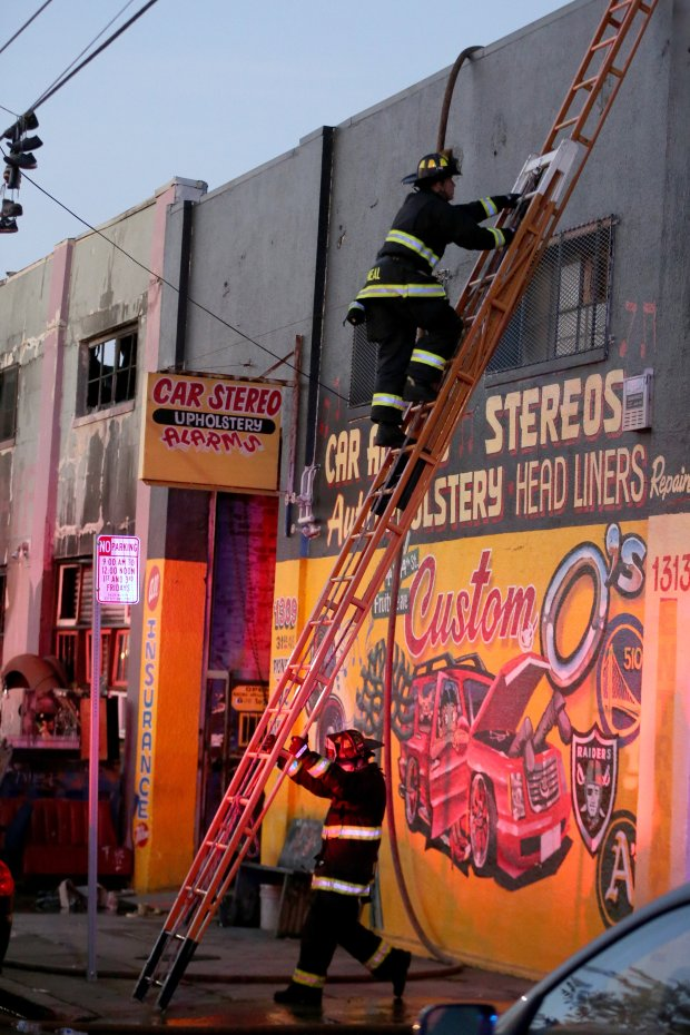 An Oakland firefighter climbs a latter to survey a fatal fire where at least nine people died during a warehouse party on 31st Avenue in Oakland, Calif., on Saturday, Dec. 3, 2016. (Ray Chavez/Bay Area News Group)