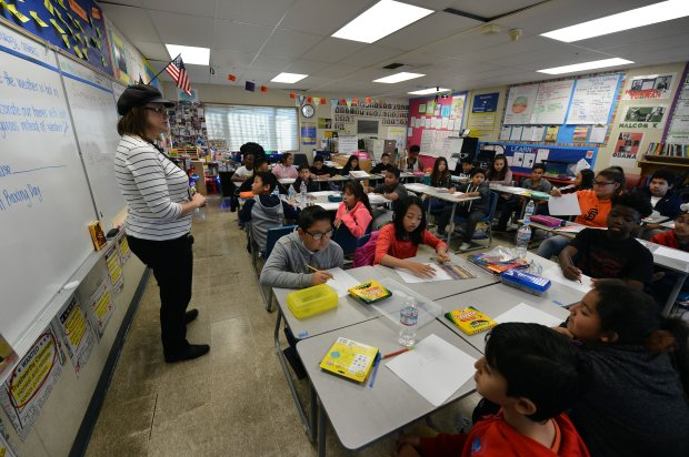Michelle Flynn, with the East Bay Center for the Performing Arts, teaches an art class in Alicia Harrison's sixth grade classroom at Wilson Elementary School in Richmond, Calif., on Thursday, Dec. 1, 2016. The school, built in 1954, is still awaiting reconstruction to be paid for by a massive bond program approved by West Contra Costa Unified School District voters starting in 1998. (Kristopher Skinner/Bay Area News Group)