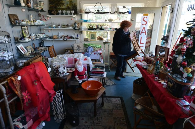 Gayle Davis gets ready for business at her Sisters Antiques shop, a mainstay for many years on Solano Ave. that will soon be closing its doors, in Albany, Calif., on Wednesday, Dec. 21, 2016. (Kristopher Skinner/Bay Area News Group)