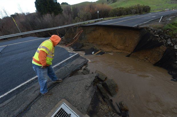 Contra Costa County Public Works Department worker Michael Dean surveys the scene of a road collapse where Pinole Creek passes under Alhambra Valley Rd. near the intersection of Castro Ranch Rd. outside of Pinole, Calif., on Wednesday, Jan. 11, 2017. (Kristopher Skinner/Bay Area News Group)