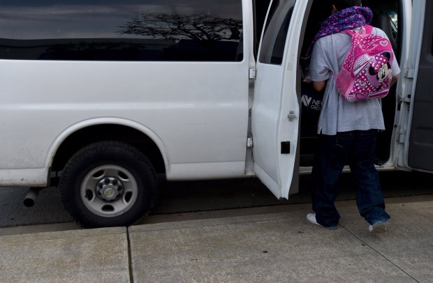 With his hands full of his families personal belongings, a father of three wears his young daughters backpack as the family enters a van at the Oasis at St. Vincent de Paul in Pittsburg, Calif., so that the family can be transported to at the Warm Winter Nights shelter set up at St. John Vianney Catholic Church on Thursday, Jan.19, 2017. Warm Winter Nights is a rotating family shelter set up during the winter months through the Social Justice Alliance and the Interfaith Council of Contra Costa County. (Susan Tripp Pollard/Bay Area News Group)