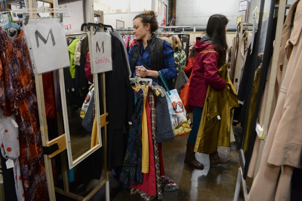 Kara Oberg, of Oakland, looks through racks of clothing at the annual 2-day White Elephant Sale in Oakland, Calif., on Saturday, March 4, 2017. The huge event offers 17 unique selling departments featuring, among other things, vintage clothing, furniture, sporting goods, books and collectibles of all kinds. (Dan Honda/Bay Area News Group)