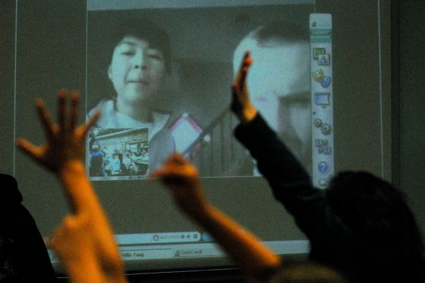Fourth-grade students raise their hands to ask their teacher Millie Wong-Tang, left, and Dr. Chris Newman, from Oxford, questions during a live talk with her classroom at Los Perales Elementary School in Moraga, Calif., on Thursday, April 16, 2009. Wong-Tang is one of 10 teachers who received a Wells Fargo Earthwatch Fellowship this year and was able to travel to the south shore region of Nova Scotia, Canada, to do field research. (Dean Coppola/Staff)