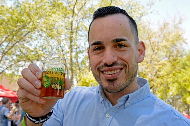 """Pedro Garcia, of Concord, holds a glass of beer while at the 8th annual Spring Brews Festival at Todos Santos Plaza in Concord, Calif. on Saturday, April 1, 2017. Garcia is an economic development specialist for the city of Concord and creator of """"Concord VIBE"""" marketing program. Garcia's job is to attract young residents and entrepreneurs to the city. (Jose Carlos Fajardo/Bay Area News Group)"""