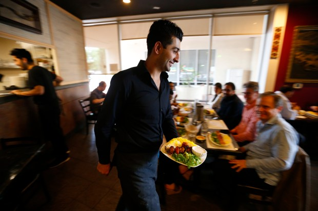 Farhad Akbarpour serves food to patrons in the dining room of Pamir on Monday, April 17, 2017, in Dublin, Calif. (Aric Crabb/Bay Area News Group)