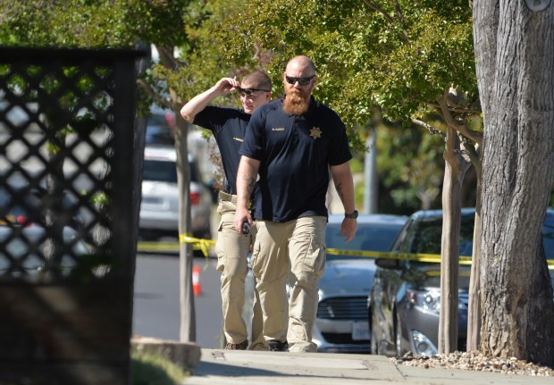 Pleasanton police walk up Touriga Drive as they talk to residents at the intersection of Burgundy Drive and Touriga Drive after an officer shot and killed an armed man in the residential neighborhood Saturday after responding to a 911 call reporting a family disturbance in Pleasanton, Calif., on Saturday, May 20, 2017. A police officer fired at the subject when the garage door of the residence on Burgundy Drive opened and revealed a man pointing a gun at the responding officers. (Doug Duran/Bay Area News Group)