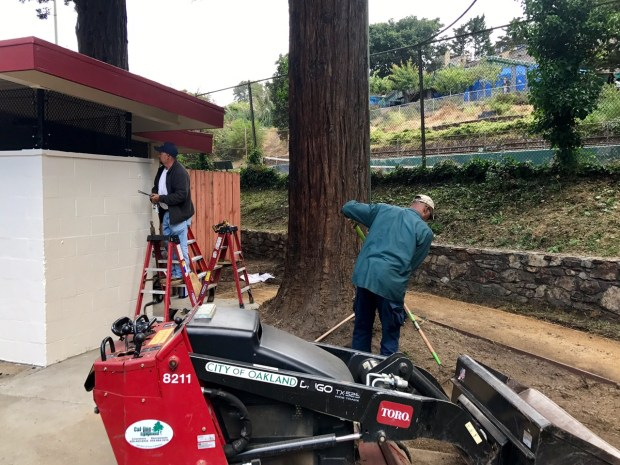 City workers clear the area next to the renovated restrooms in Montclair Park.