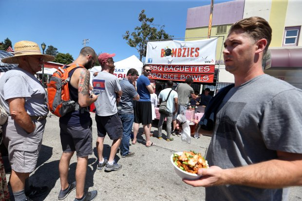 Festivalgoers stand in line to order food at one of the several food vendor tents during the 17th annual Laurel Street Fair in Oakland on Aug. 13, 2016.
