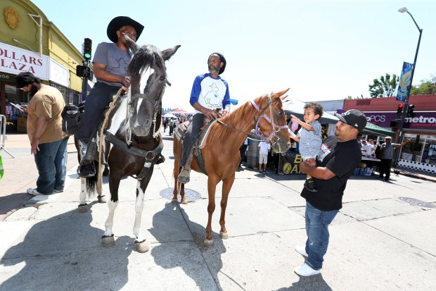Doug Jones, left, atop Ice, and owner of DJ's Martial Arts & Fitness of Oakland, and Duggar Mathews atop Veronica, are greeted by festivalgoers Andy Santos, 3, and his father Victor Santos, of Oakland, during the 17th Annual Laurel Street Fair in Oakland on Aug. 13, 2016.