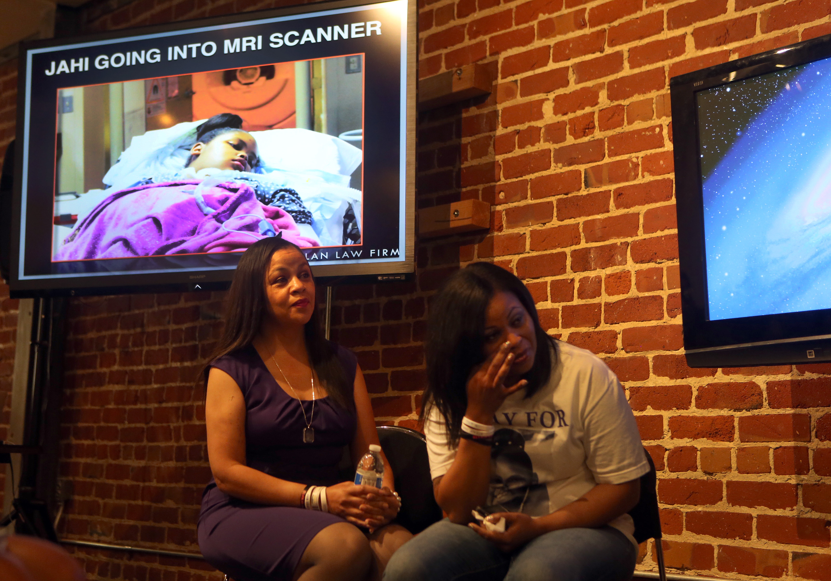 In this Oct. 2, 2014 file photo Sandra Chatman, left, and Nailah Winkfield look on as a photo of their granddaughter and daughter, respectively, Jahi McMath, 13, is shown during a press conference at Dolan Law Firm in San Francisco, Calif. Christopher Dolan, attorney for Jahi McMath's family, showed photos and a pair of videos where McMath moves her foot and arm in response to the voice of her mother Nailah Winkfield in a home in New Jersey. She was declared brain-dead in California after tonsil, throat and nose surgeries to relieve her sleep apnea. (Ray Chavez/Bay Area News Group)