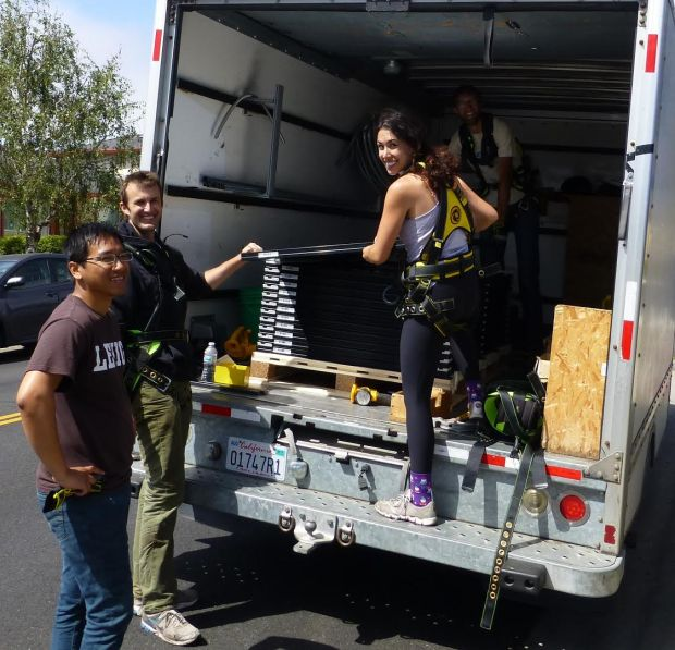 (Photo courtesy of DougMcKenzie) SunWork volunteers Dean Weng, Newton Oldfather and Aubrey Beltran unload panels from a truck in Berkeley on July 29, 2017.