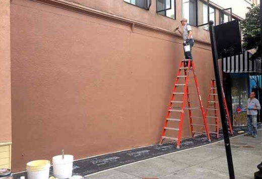 A worker paints to top of where the Vallejo Rising mural used to be on Marin and Georgia streets. (John Glidden — Times-Herald)
