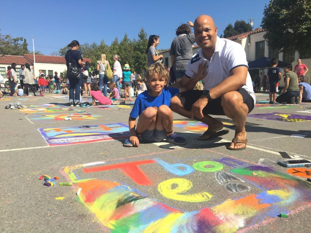 Mike Ero and his 9-year-old son, Thomas Ero, enjoyed the Chalk Art Festival at Beach Elementary School in Piedmont. This was their fourth year at the event. Thomas Ero signed his artwork with his nickname, T-Bone, on a square. (Sarah Tan/For Bay Area News Group)