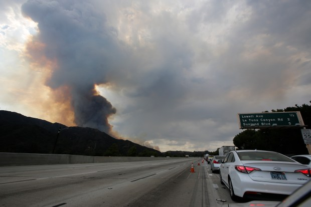 A plume of smoke is seen from the 210 Freeway as a brush fire burns in the Verdugo Mountains in the Sun Valley neighborhood of Los Angeles. (AP Photo/Damian Dovarganes)