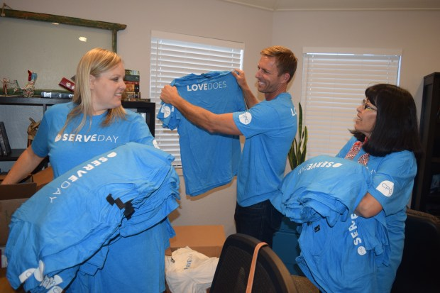 "Community Presbyterian Church staff members Deana Dickerson, left, and Bianca Canales, right, along with Senior Pastor Tyler Scott, sort some of the hundreds of T shirts volunteers taking part in this weekend's ""Serve Day"" will be wearing at 20 different work sites around the East Bay."