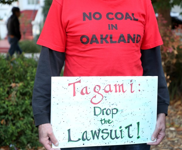 Protester Michael Kaufman holds a sign during a rally near developer Phil Tagami's home to protest a coal terminal at the Port of Oakland on Monday, Oct. 30, 2017, in Oakland, Calif. Tagami sued the city of Oakland after the City Council voted to ban the transport of coal through Oakland in 2016. (Aric Crabb/Bay Area News Group)