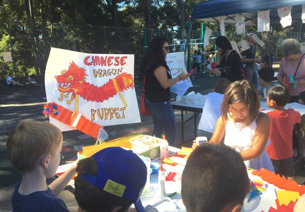 Children make Chinese dragon puppets at an activity booth at Joaquin Miller Elementary's annual World Culture Festival. (Sarah Tan/For Bay Area News Group)