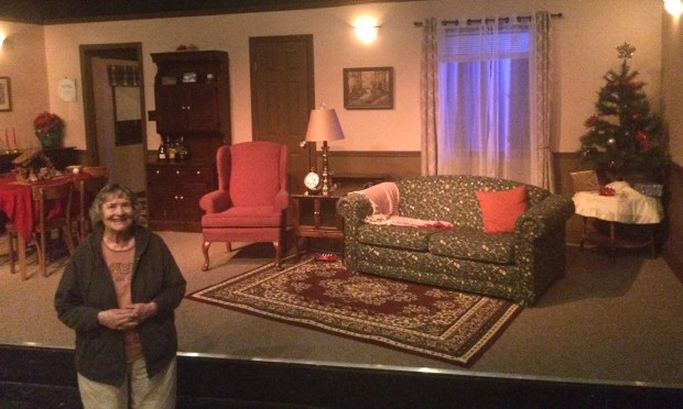 """Helen Means stands in front of the set for """"Greetings,"""" one of the shows that Onstage Theatre is producing in its 40th season."""