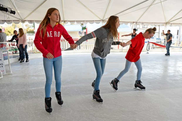 From left, Pearl Rounsaville, 13, Emilee Knight, 13, and Amber Wilkinson, 13, all of Brentwood, hold hands while enjoying Brentwood on Ice in Brentwood, Calif. on Saturday, Nov. 18, 2017. This is downtown Brentwood's first ice rink. (Jose Carlos Fajardo/Bay Area News Group)