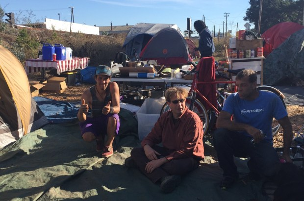 "Trevor ""T.Rex"" Sullivan, Sam Clune and Jay DeMello relax at a homeless camp along Bay Street and the Union Pacific tracks in Berkeley's Aquatic Park on Nov. 7, 2017. (Tom Lochner)"