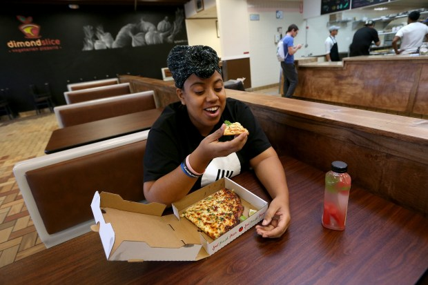 Customer Sarah Bellot, who works nearby, eats at Dimond Slice Pizza in Oakland, Calif., on Monday, Nov. 20, 2017. Co-owners Artemio Maldonado and Dwight Ferron, alums of Cheese Board Pizza in Berkeley's Gourmet Ghetto, opened the restaurant in Oakland's Dimond District on Nov. 15. They feature vegetarian and vegan pizza and make a different type pizza each day. (Jane Tyska/Bay Area News Group)
