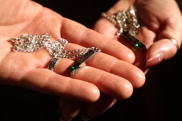 David Gregory, left, and his wife Kim hold pendants with the ashes of their daughter Michela, on Tuesday, Nov. 28, 2017, in South San Francisco, Calif. Michela Gregory died in the Ghost Ship fire on December 2, 2016. (Aric Crabb/Bay Area News Group)