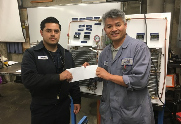 Carlos Jimenez, left, a College of Alameda student, receives a $500 check from College of Alameda automotive department instructor Wayne Fung for the Ozzie Day Scholarship, an award given to the highest achieving student in the department.