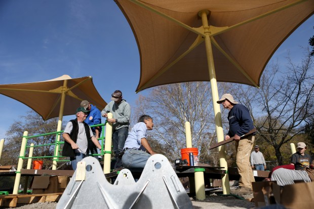 Volunteers assemble a play structure for an all access playground being built at Moraga Commons Park, in Moraga, Calif., on Saturday, Dec. 9, 2017. The Rotary Club of Moraga raised more than $240,000 for the 5,000-square-foot playground. (Anda Chu/Bay Area News Group)