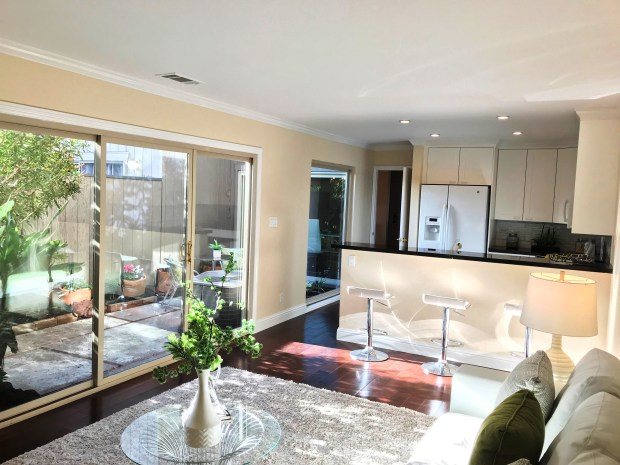 The remodeled white kitchen features dark stone counters and the patio keeps the living airy and bright.