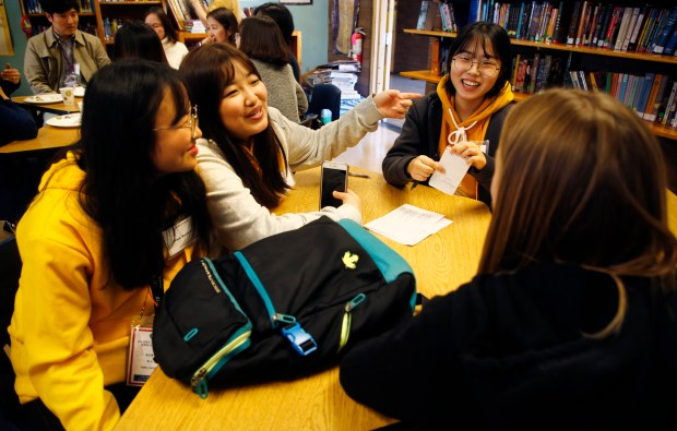 South Korean students, from left, Su yeon Park, 16, Yujin Cha, 16 and Chaeyun Park, 16, talk with Academy of Alameda student Stella Cashin, 13, in Alameda, Calif., on Monday, Jan. 22, 2018. Twenty middle school age students from the Yeongdong area of South Korean, Alameda's sister city, visits the school to get a glimpse of what American schools are like. (Laura A. Oda/Bay Area News Group)