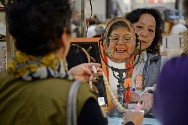Carolyn Burgess, of Oakland, is reflected in a mirror as she shops for jewelry while being assisted by volunteer Peggy Woon during a preview sale for the 59th annual White Elephant Sale in Oakland, Calif., on Sunday, Jan. 28, 2018. Funds raised by the event support the Oakland Museum of California. The event is organized and presented by Oakland Museum's Women's Board and has raised more than $2 million for each of the past three years. The White Elephant Sale will be held on March 3rd and 4th. (Jose Carlos Fajardo/Bay Area News Group)