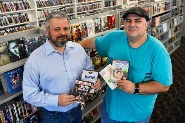 Take One Video store owners Jason Wood, left, and Tony Ibrahim are photographed holding some of their favorite movies at their store in Pleasant Hill, Calif., on Friday, Jan. 5, 2018. After being in business for 18 years Take One Video will be closing their doors on January 20th. (Jose Carlos Fajardo/Bay Area News Group)